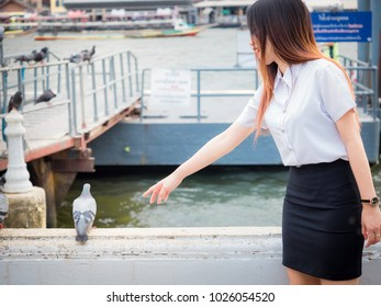 student and gradutation concept from portrait of asian beautiful girl(20s to 30s) with long black hair smile and happiness feeling for feeding to the bird with river background