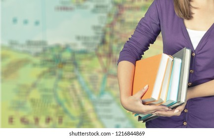 student hand with books and map, learn