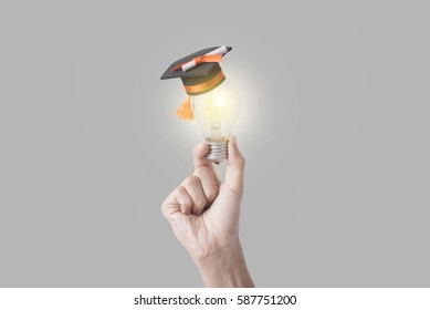 student hand holding light bulb with graduation hat on gray background. concept education of new ideas with innovation and creativity.