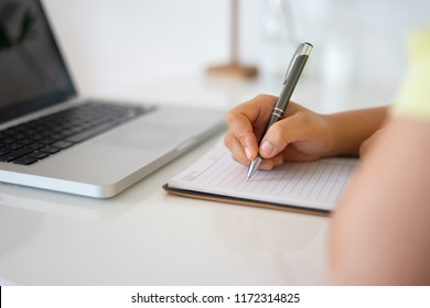 Student hand holding pen writing doing examination in university ,students in uniform attending exam classroom educational school: Young female business writes information note from portable net-book