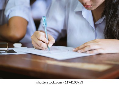 Student hand holding pen writing doing examination in university ,girl in uniform attending exam classroom educational school: college people in room ,Scholarship test for Study abroad