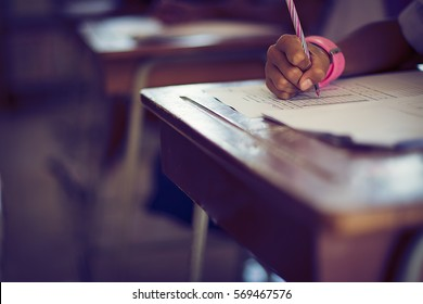 Student hand holding pen writing doing examination with blurred abstract background university students in uniform attending exam classroom educational school