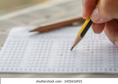 Student hand testing doing test exam with pencil drawing selected choices on thai alphabet answer sheets in final exams at college or university. Taking multiple choice for assessment in examination