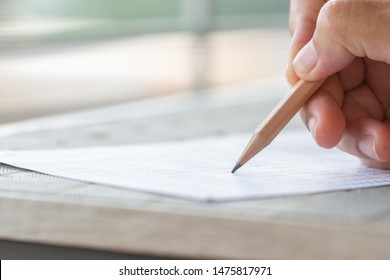 Student hand testing doing test exam with pencil drawing selected choices on answer sheet in school final exams at college or university. Taking multiple choice for assessment in examination classroom