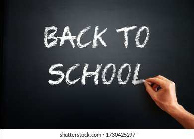 Student hand write tittle BACK TO SCHOOL, white chalk text on black school board.