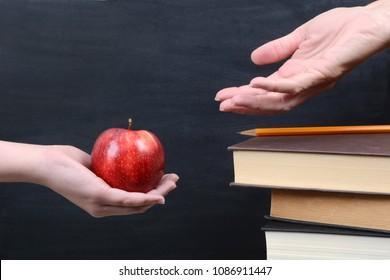 student handing an apple to the teacher
