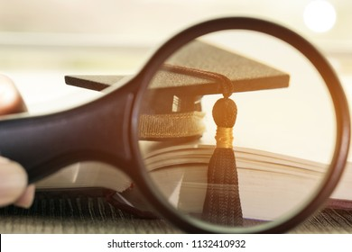 Student hands holding magnifying glass on book document have Graduation cap on Books in Library room of campus and university. Concept of Graduate abroad international Educational and Back to School.