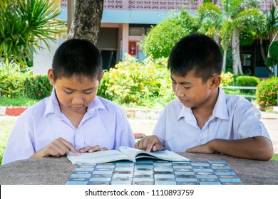 student  happy to reading book together on concrete table in the school