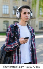 Student in headphones with backpack on shoulder listening to songs