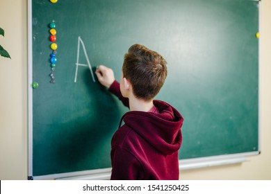 Student of higer school is standing in dark hoodie near the green blackboard in the classroom. Teenage Boy is writing alphabet on the board. School education concept.