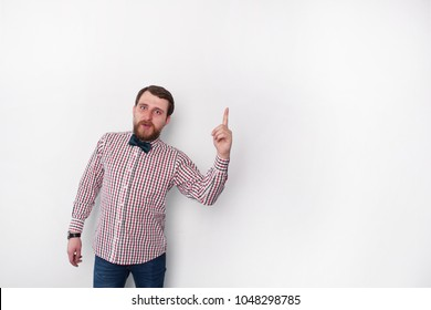 Student and his astonishment. Young bearded handsome student with bow tie showing eureka sign in studio with white background. With copyspace