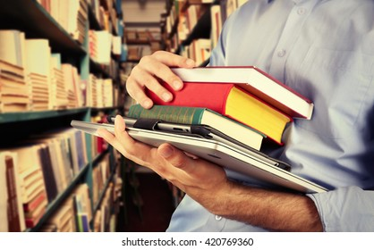 Student holding books and laptop in library