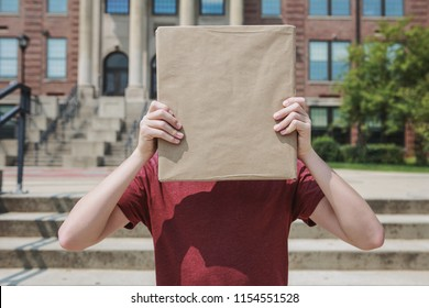 Student holding kraft paper covered text book in front of face at school, hidden identity