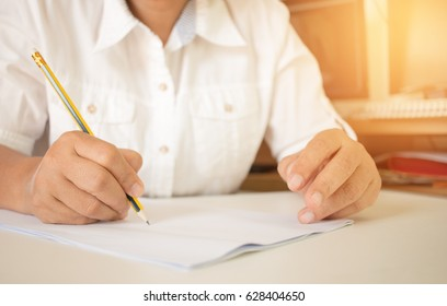 student holding pencil writing test in exercise, exams answer sheets in classroom, educational school