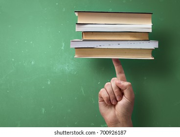 A student holding up study books with a single finger. Fast successful learning concept.