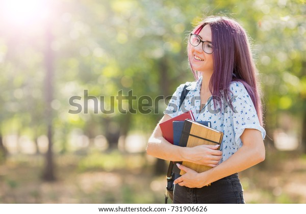 Student holding textbooks on a natural background. Girl with books. Learning concept. Copy space.