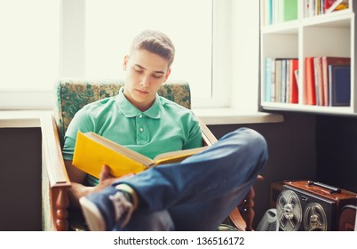 Student at home sitting on chair and reading book