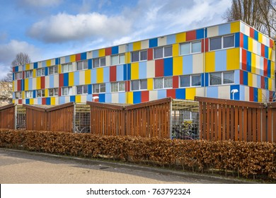 Student housing in shipping containers painted in pright colors with bicycle parking in the foreground