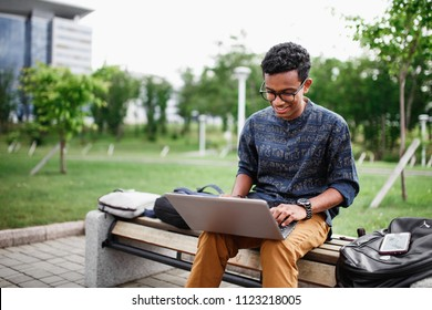 A student from India sits with a laptop in the Park and smiles. Students live and study on campus. The photo illustrates education, College, school, or University.