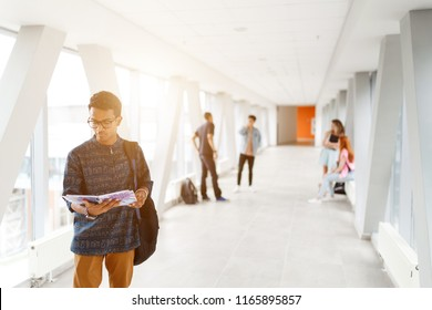 A student from India stands with a book at the University. Students in the background. The photo illustrates education, College, school, or University.