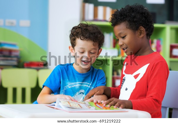 Student in international preschool reading a magazine book together in school library, education, kid and study concept