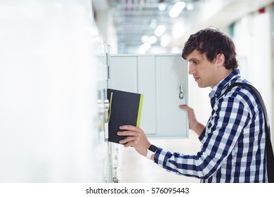 Student keeping his book in the locker in university