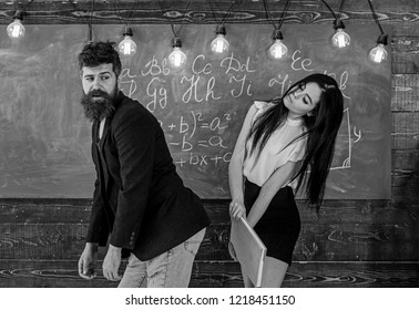 Student lady slapping on teachers buttocks with book. Girl on smiling face having fun while punishes teacher. Role games concept. Man with beard punished by sexy student, chalkboard on background.