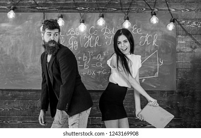 Student lady slapping on teachers buttocks with book. Role games concept. Man with beard punished by sexy student, chalkboard on background. Girl on smiling face having fun while punishes teacher.