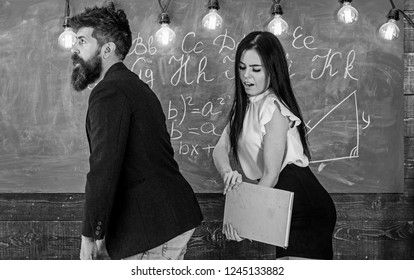 Student lady slapping on teachers buttocks with book. Role games concept. Girl on smiling face having fun while punishes teacher. Man with beard punished by sexy student, chalkboard on background.