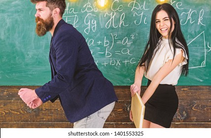 Student lady slapping on teachers buttocks with book. Girl on smiling face having fun while punishes teacher. Man with beard punished by sexy student, chalkboard on background. Role games concept.