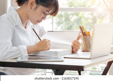 Student learning online study concept: Beautiful Asian girl learning and writing in textbook or homework, short notes with laptop, pencils box on desk in home for e-learning near window background