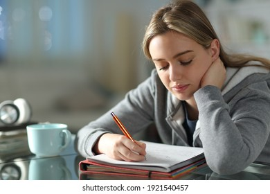 Student learning taking notes in the night in the living room at home
