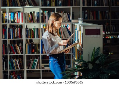 Student in library - smiling young female teenager search a book stand at bookshelf n college library. Sweden woman student picking literature for education checking information in books store.