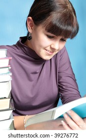 Student in a library surrounded by piles of books