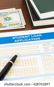 Student loan application form with pen, dollar banknote, and text book