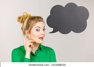 Student looking business woman wearing green shirt talking, black thinking bubble on grey background.