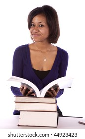 A student looking at her book with a smile on her face.