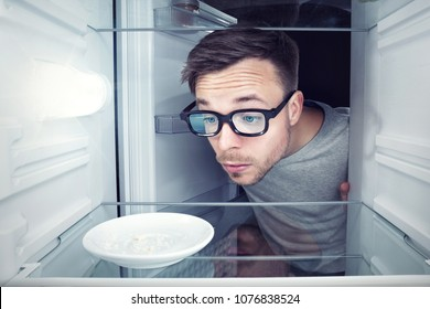 Student looking inside an empty refrigerator