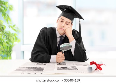 Student looking for a job in a newspaper at home with a magnifying glass