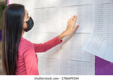 Student is looking for a name from the exam results on the board. At university ,Back to school concept.