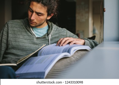 Student making notes from a reference book sitting on a couch. Young man studying seriously sitting at home.