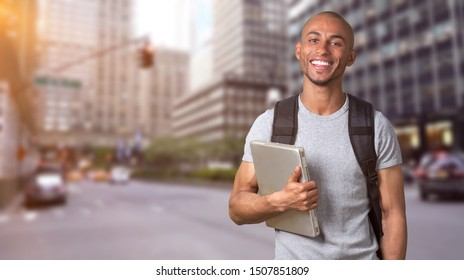 Student man with laptop smiling at camera