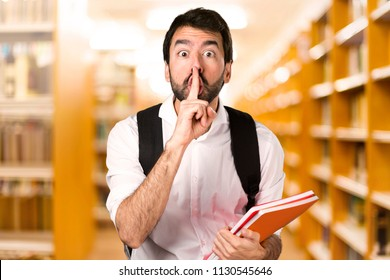 Student man making silence gesture on defocused library