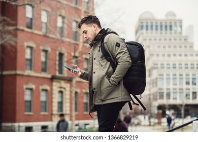 Student man text on cell phone walking in city college campus with backpack