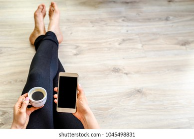 Student with mobile phone and coffee. Hand holding modern smartphone with screen in black. People using internet for working home or online shopping, lifestyle concept
