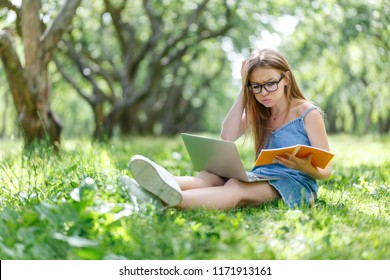 Student with notebook in park looking at computer
