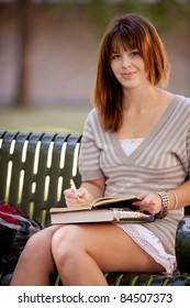 Student on bench taking notes in a journal