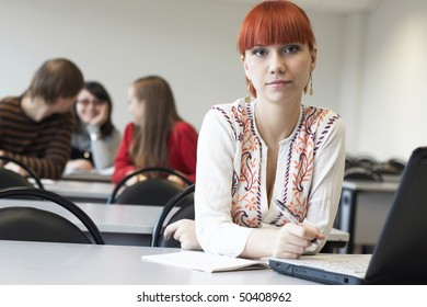The student on employment in a class room sits at a table