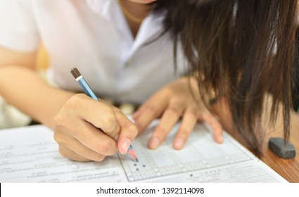 Student with a pencil taking final test in the examination room - educational or academic concept image of test taker in the training or learning room at collage of university campus, selective focus