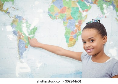 Student pointing to a map of the world at the elementary school
